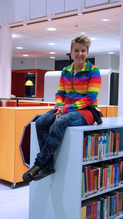 Pia Rask-Jussila istuu uudistetuissa Joensuun pääkirjaston lasten ja nuorten tiloissa kirjahyllyn päällä hymyillen iloisesti.