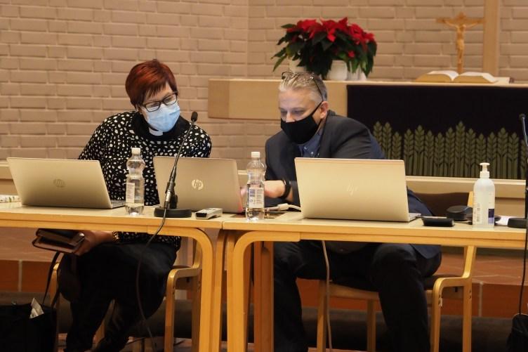 Yhteisen kirkkoneuvoston puheenjohtaja Tiina Reinikainen ja Joensuun seurakuntayhtymän hallintojohtaja Tommi Mäki istuvat tietokoneiden ääressä ja tutkivat papereita. Molemmilla on maskit kasvoillaan.