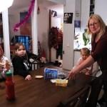 Kolme lasta istuu pöydän ääressä syömässä paahtoleipää. Äiti Niina Väätäinen kattaa pöytää ja katsoo kameraan.