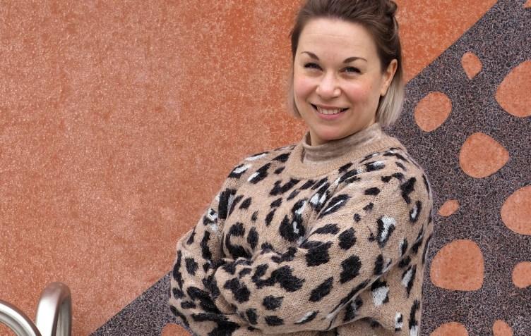Sosiaaliohjaaja Tanja Ikonen seisoo terrakotanvärisen seinän edessä katsoen kameraan hymyillen.
