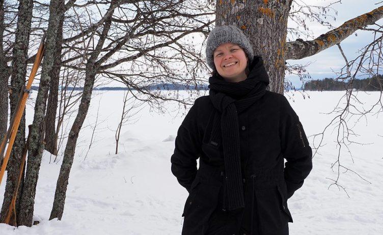 Ruut Hurtig nojaa puuhun Pielisen rannassa Paalasmaalla. Takana näkyy luminen järvimaisema. Hurtig katsoo hymyillen kameraan.