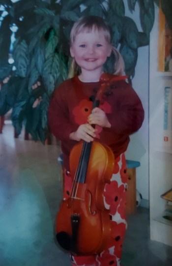 2-vuotias Marika seisoo viulun kädessään ja nauraa iloisesti kameraan katsoen.