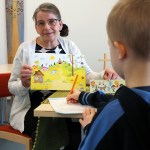 Lastenohjaaja Helena Leppänen esittelee kädessään olevaa pyhäkoulutaulua pojalle, joka seisoo selin kameraan.