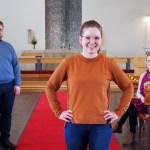 Emilia Rösch, Antti Kyytsönen ja Katja Nuukarinen kuvattuina Pielisensuun kirkon kirkkosalissa. Etualalla seisoo Rösch kädet lanteilla ja katsoo hymyillen kameraan.