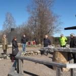 Seitsemän ihmistä seisovat Kiihtelysvaaran rauniokirkon ristin lähellä.