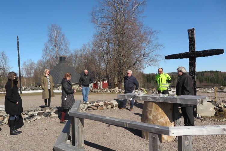 Seitsemän ihmistä seisomassa Kiihtelysvaaran rauniokirkon ristin lähellä.