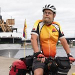 Mieshenkilö polkupyörän kanssa joen rannalla.