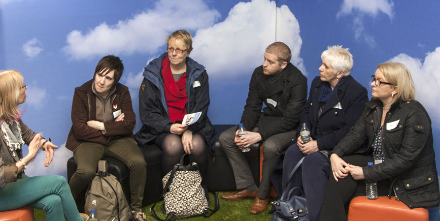 Comoodle Tour group sitting in front of images of a blue sky with fluffy white clouds