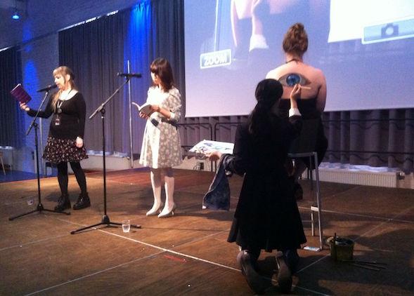 Runoilija Yumi Fuzuki luki runojaan japaniksi, suomentajs Mayu Saaritsa käänsi ne yleisölle samanaikaisesti kun kuvataiteilija Hikaru Cho maalasi mallin selkään.