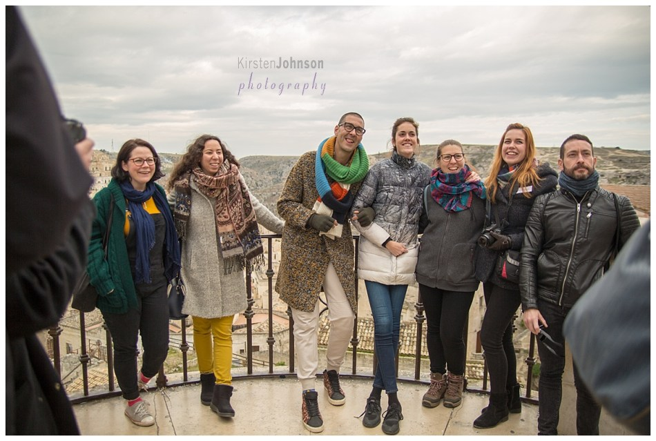 A group of people standing on a balcony overlooking the city of Matera