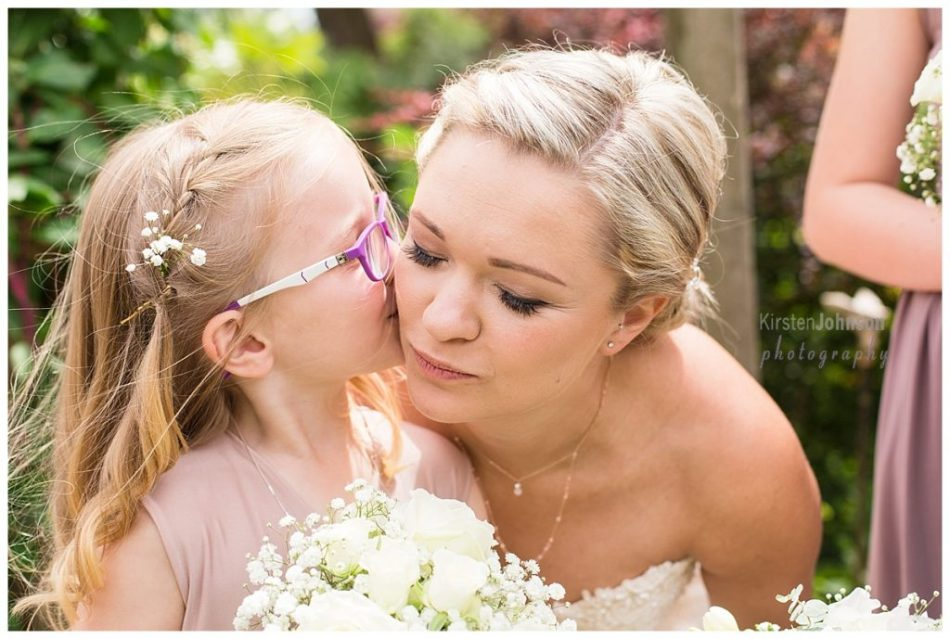 Flower girl kissing bride on cheek