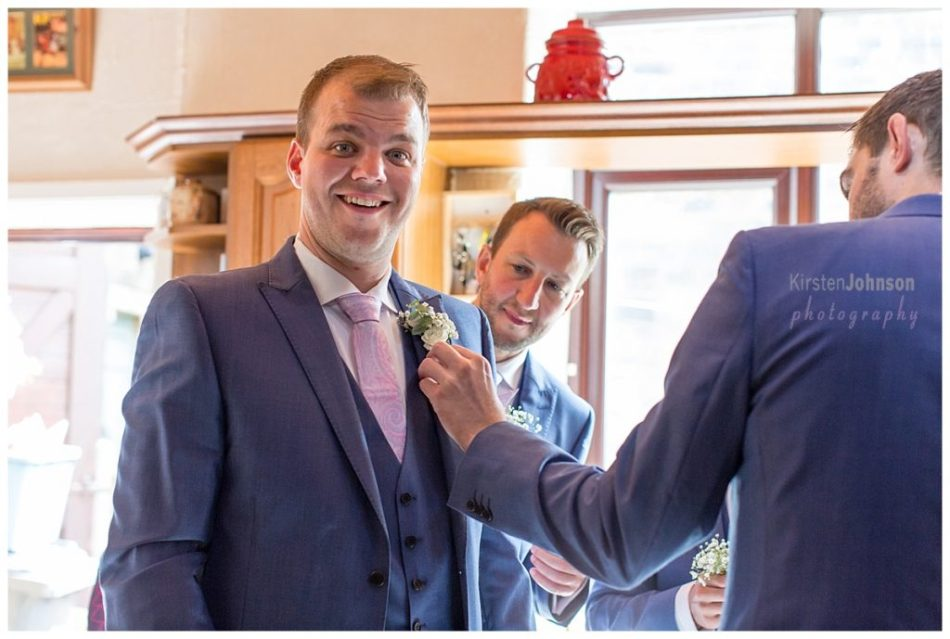 groom getting button hole put on suit