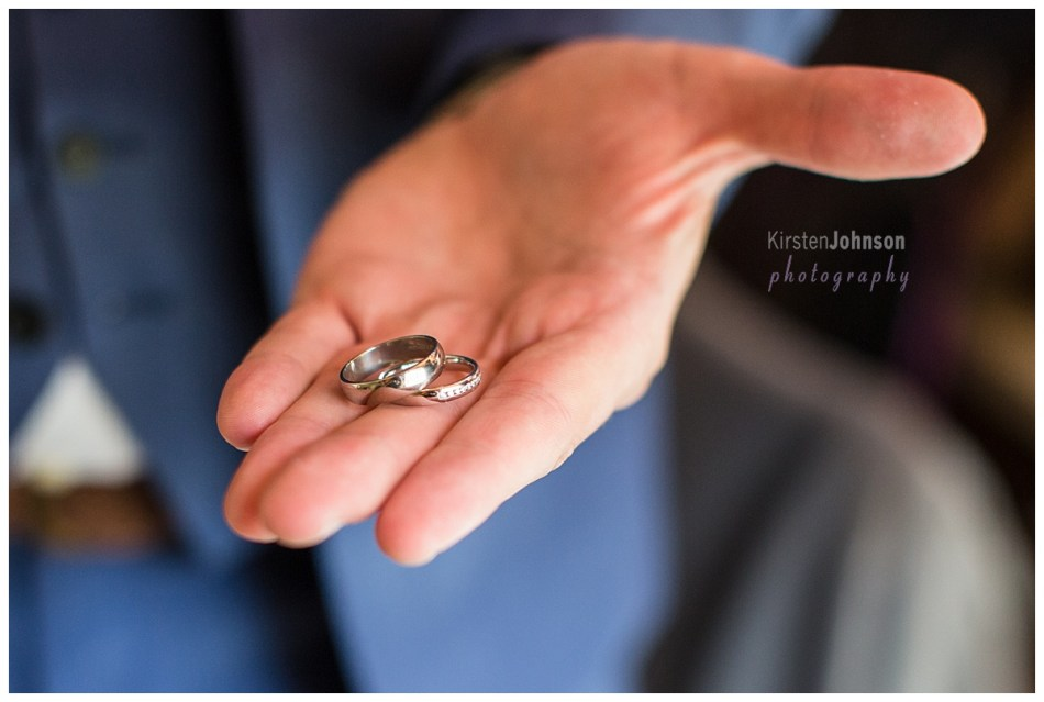close up of wedding rings in grooms hand