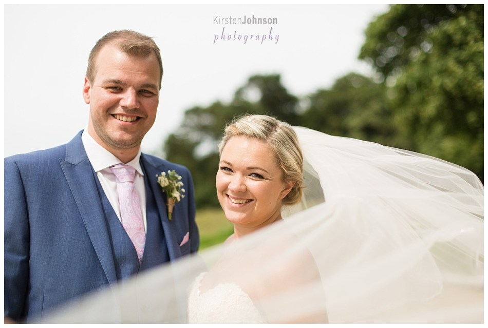 bride and groom portrait with veil in wind