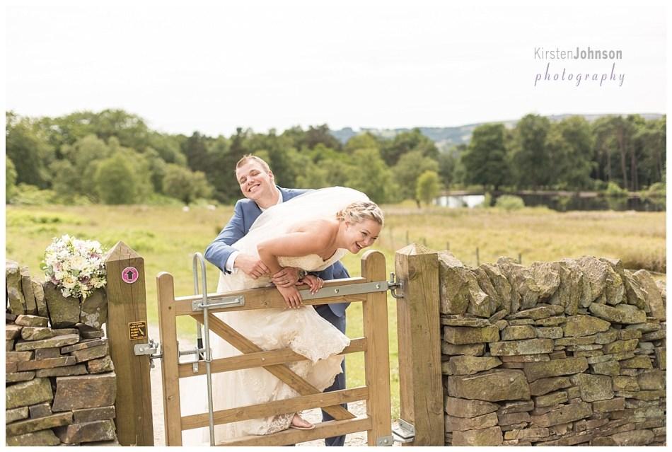 groom lifting bride onto gate