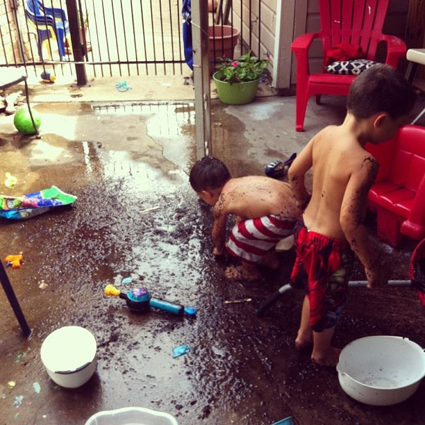 The boys destroying my back patio with mud made from a bag of potting soil, mixed with the water I gave them to play with.
