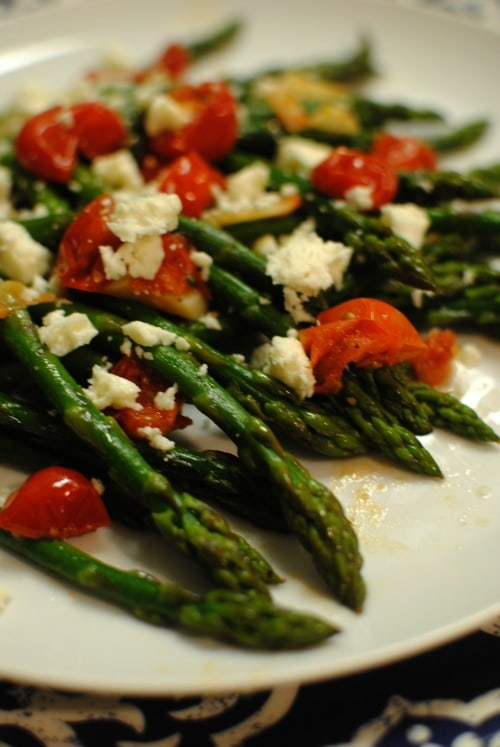 Quick and delicious asparagus with garlic, burst tomatoes, and feta.