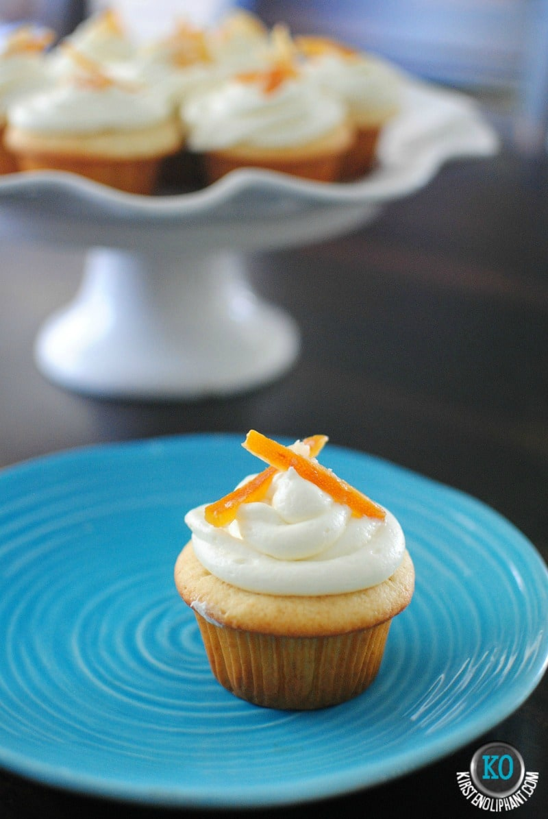 Creamy, light, and a bit of zing!  Champagne cupcakes with ginger-orange frosting and candied ginger & orange peels.