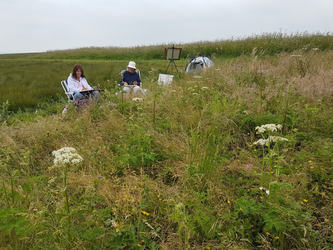 artists sketching in a meadow with dog tent