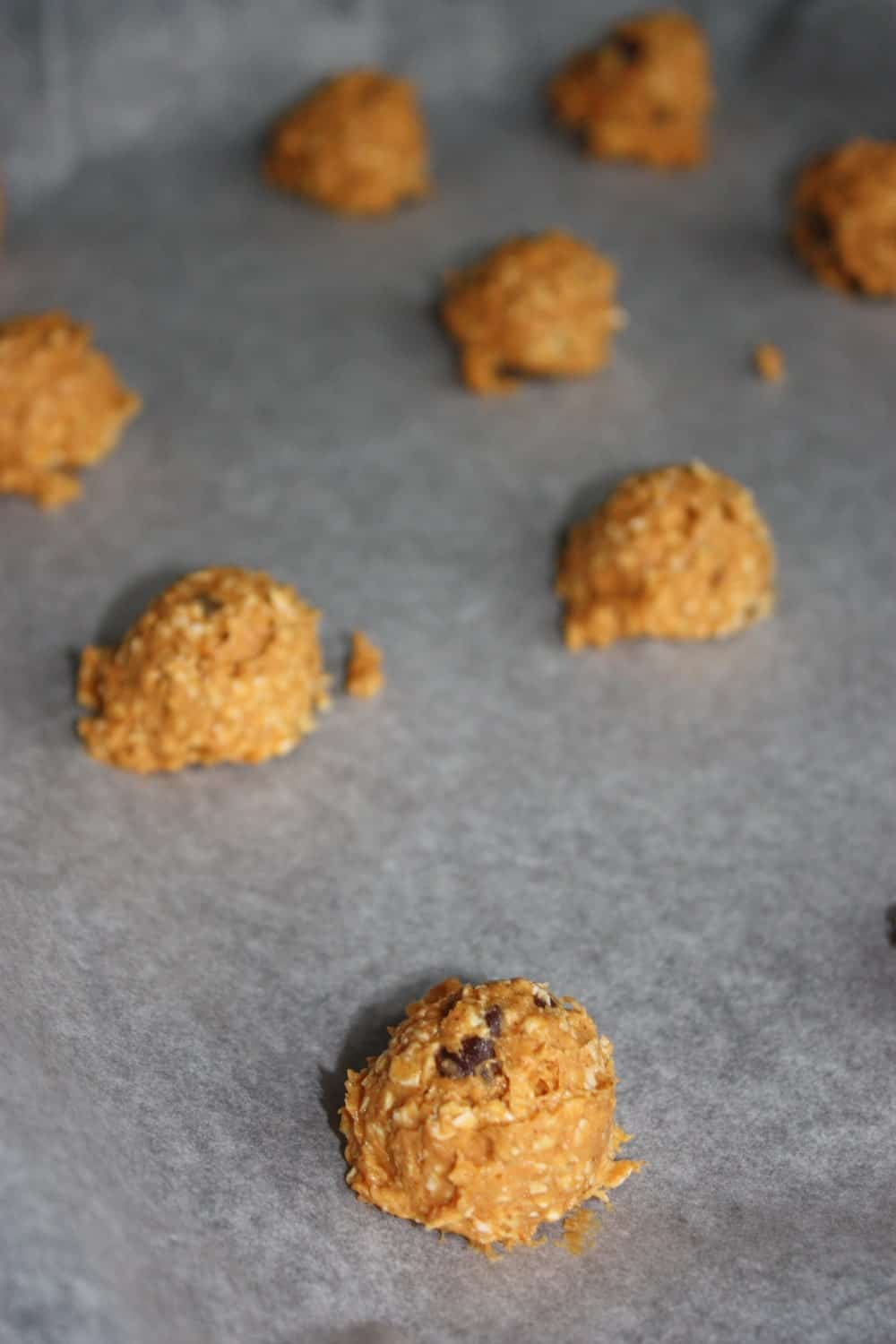 Scooping the cookies onto the parchment paper.