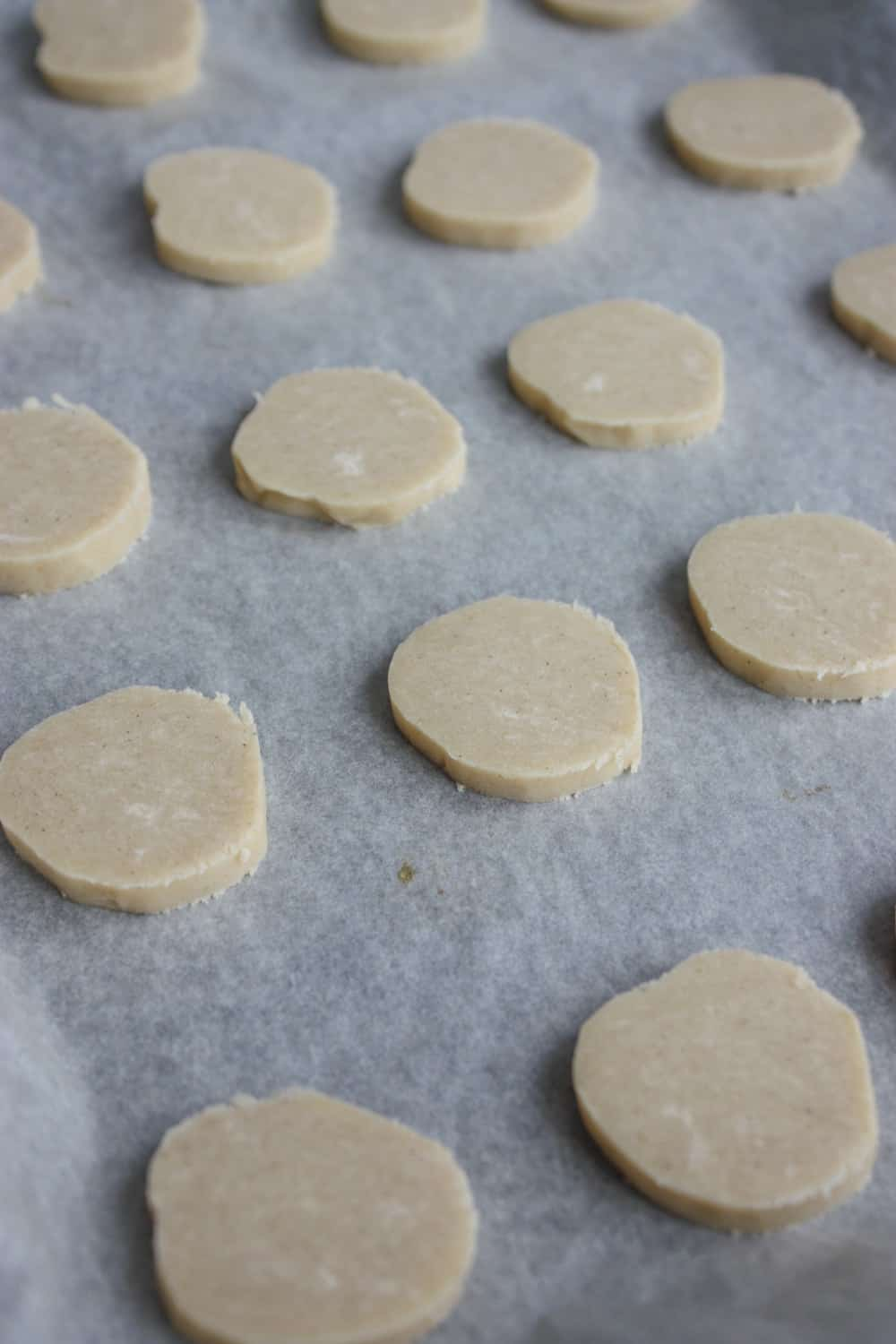 Placing cookies on parchment paper lined baking sheet.