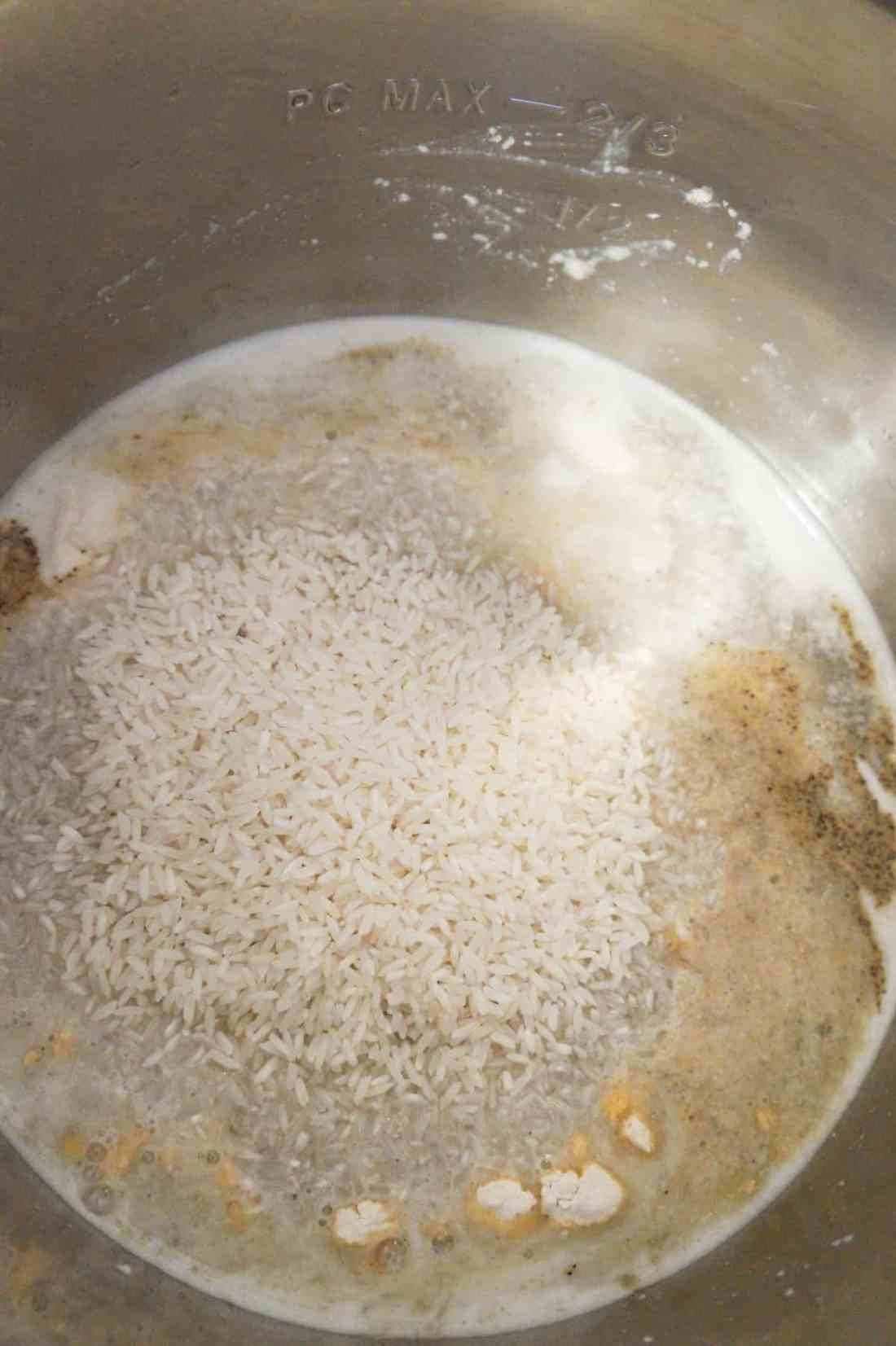long grain rice on top of chicken, water and spices in an Instant Pot