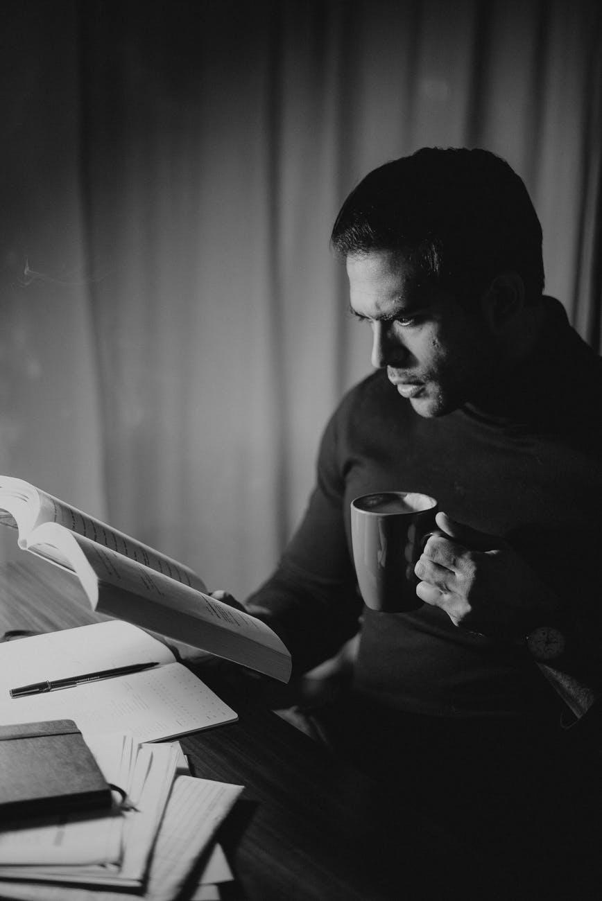 frowning man reading book late at night