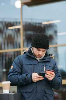 serious man using plastic card while making online shopping on smartphone on street