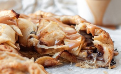 A caramel chocolate apple galette with a piece missing