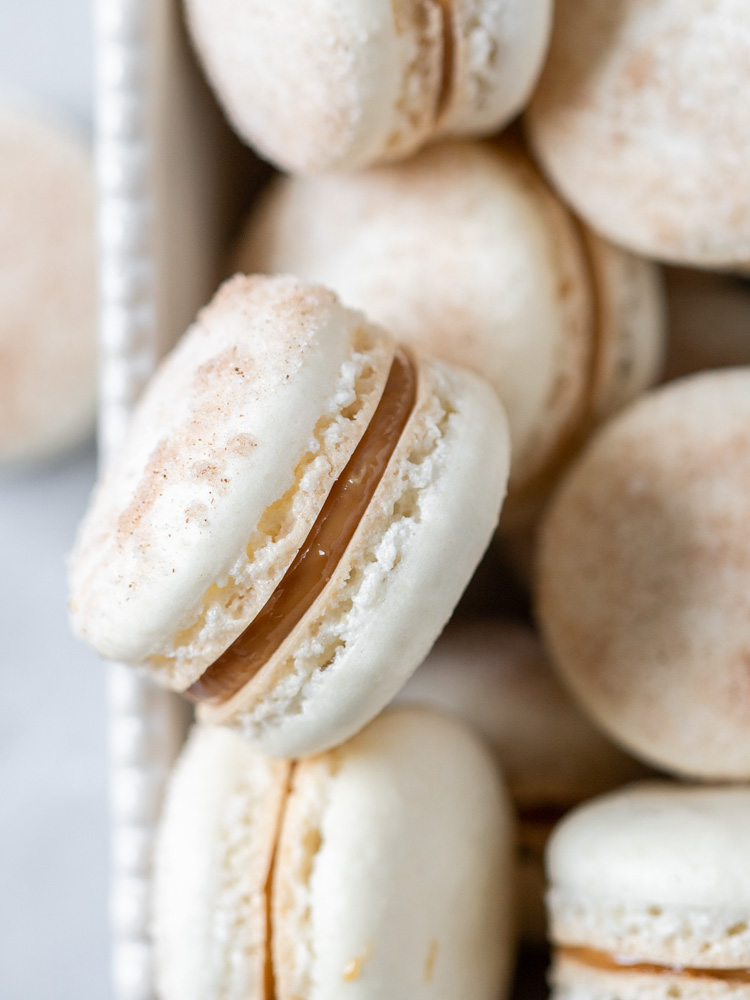 A close up look on a churro macaron with glossy dulce de leche filling