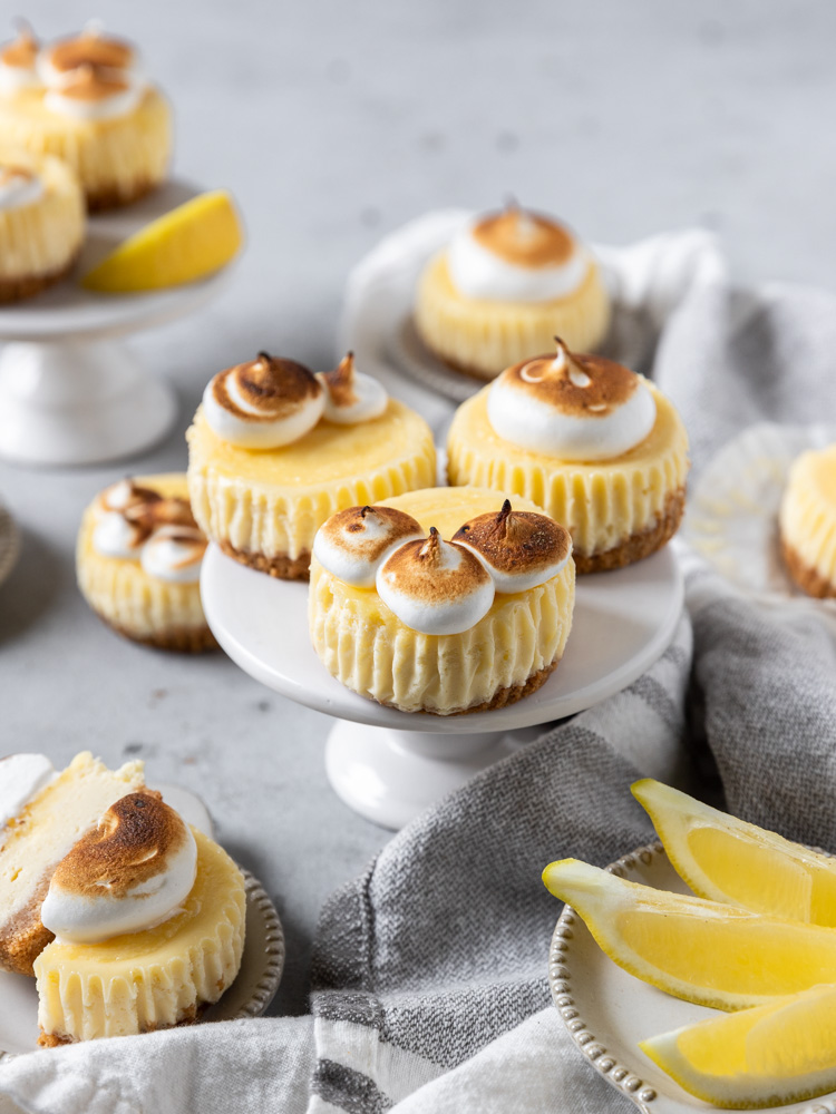 Mini lemon cheesecakes on a small pedestal surrounded by other cheesecakes