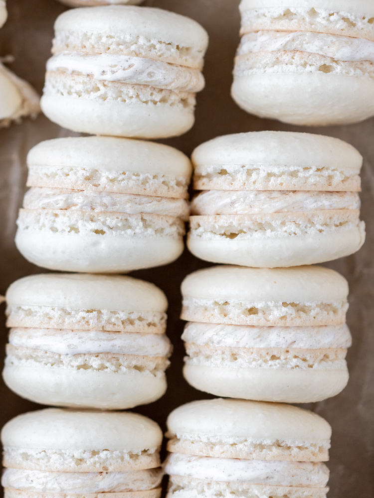 Looking down on two rows of fluffer nutter macarons. They have white shells and a swirled filling