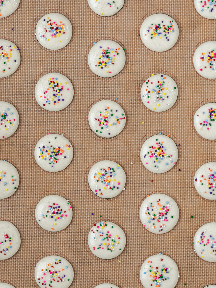 The macarons piped on a baking sheet and topped with sprinkles