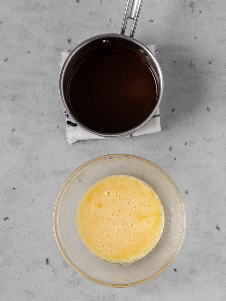 The melted chocolate in a saucepan and the egg yolk mixture in a bowl