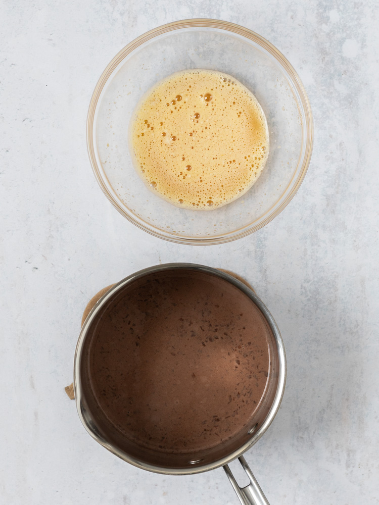 the egg mixture in a bowl and the chocolate mixture in a sauce pan