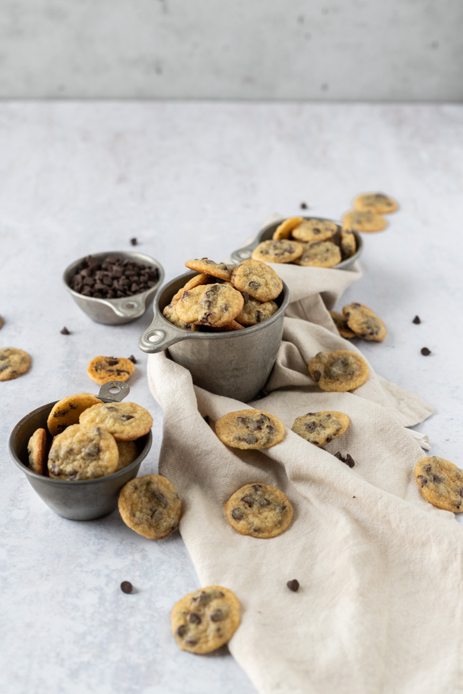 tiny chocolate chip cookies scattered around cups holding more cookies