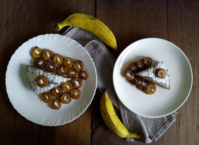 Eggless Banana Cake, dusted with powdered sugar and accompanied by deep-fried ripe nendran banana chips.