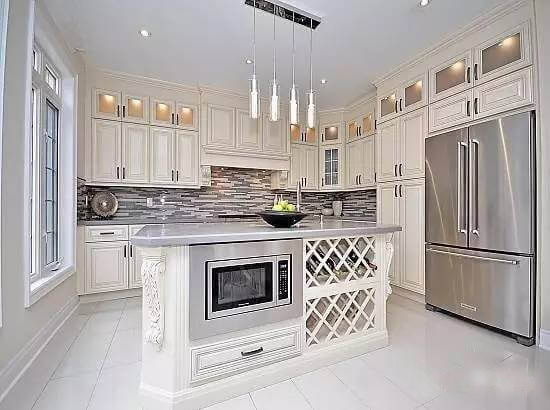 White kitchen with island and microwave, pearl cabinets and stainless fridge