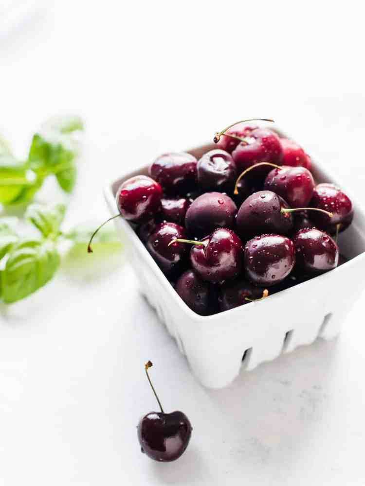 Fresh cherries in a white ceramic box with basil leaves in the background to make Cherry Basil Sorbet