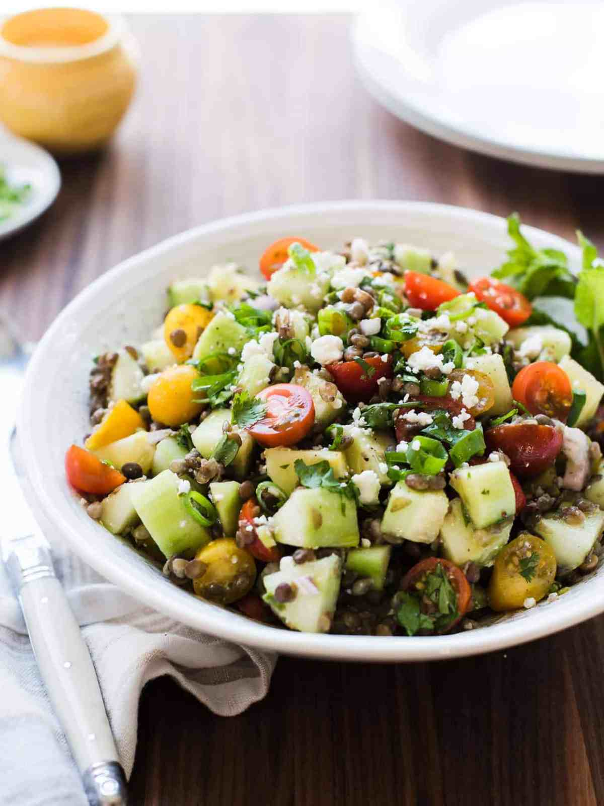 Summer Lentil Salad with lentils, cucumbers, tomatoes, and mint in a white bowl.