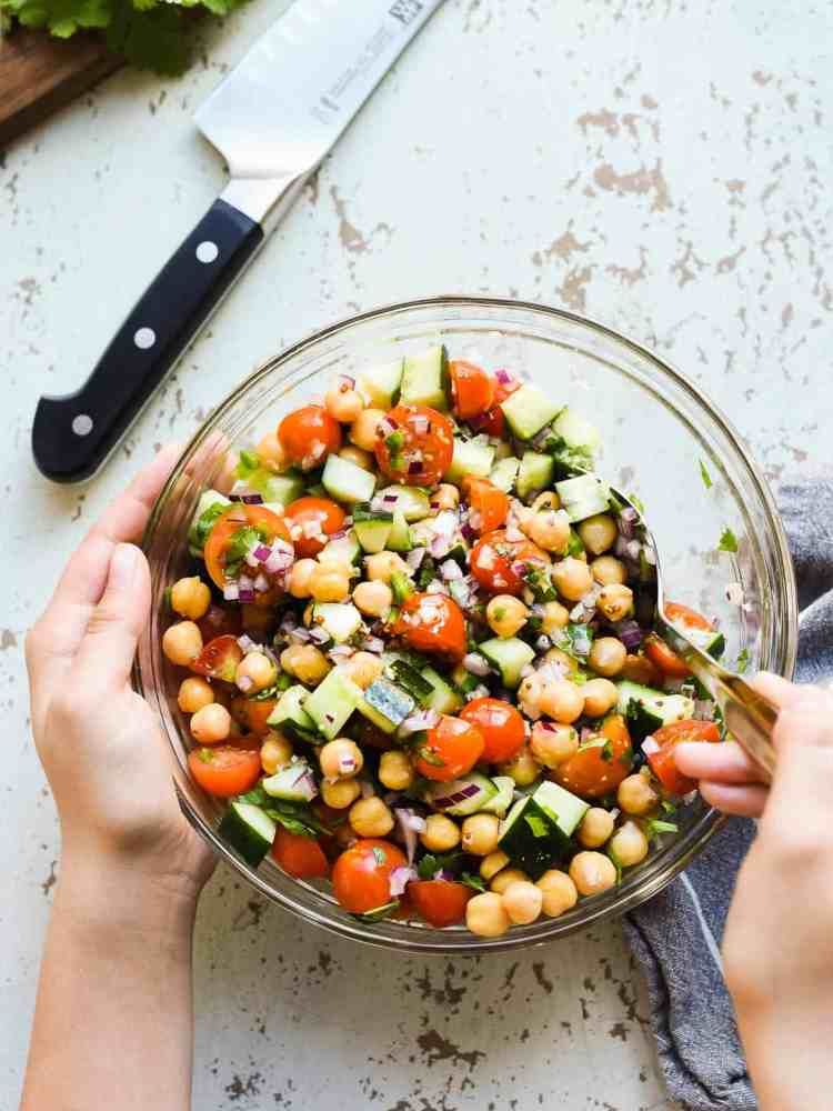 chick pea salad with tomatoes and cucumbers in a glass bowl on a rustic white background with hands holding the bowl