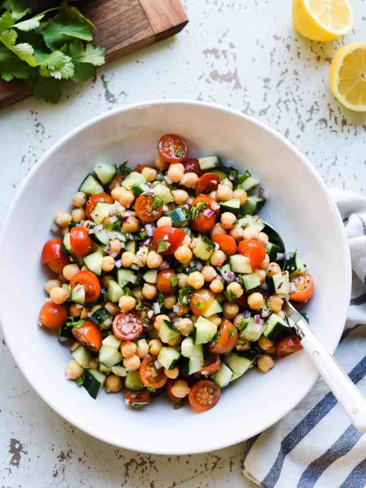 chick pea salad with tomatoes and cucumbers in a white bowl on a rustic white background