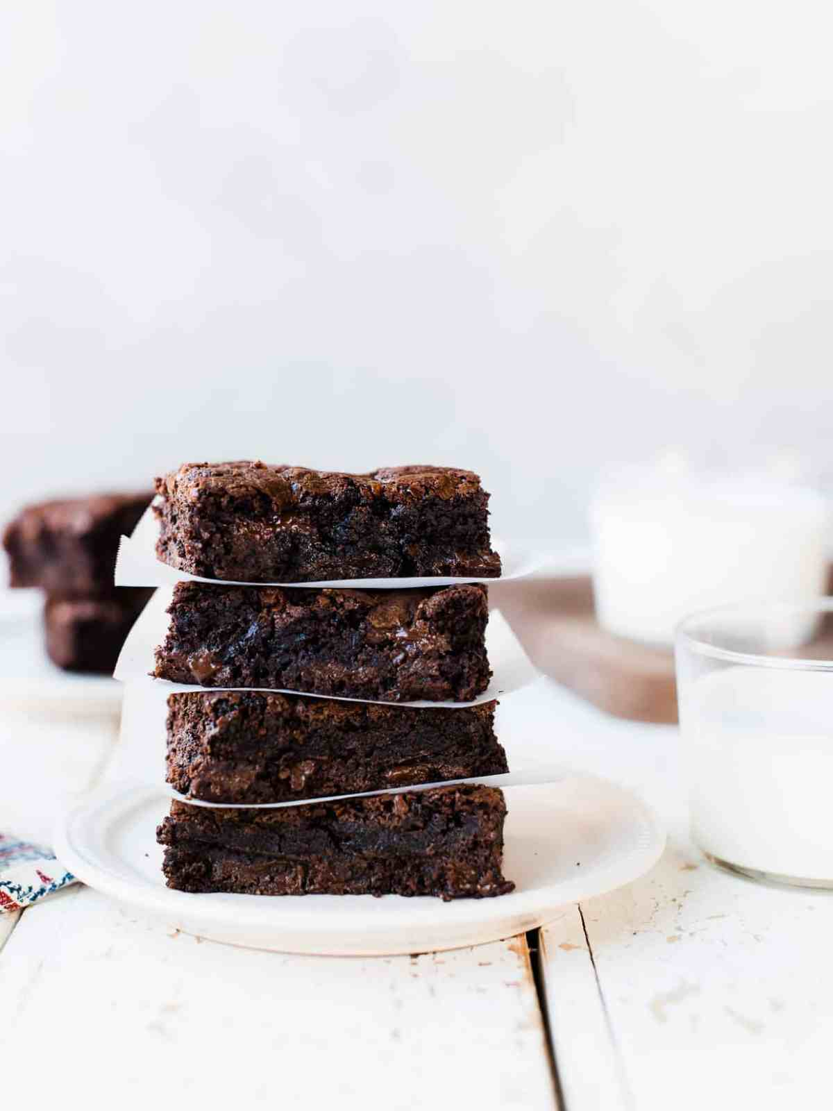 Stack of decadent homemade brownies on a plate, with parchment paper.