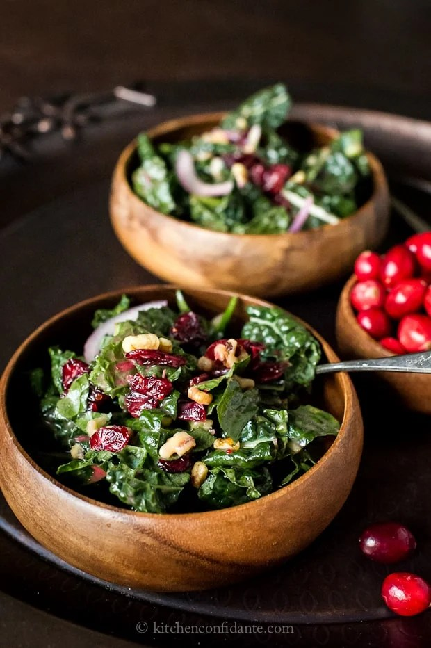 Cranberry Walnut Kale Salad in wooden bowls with fresh cranberries