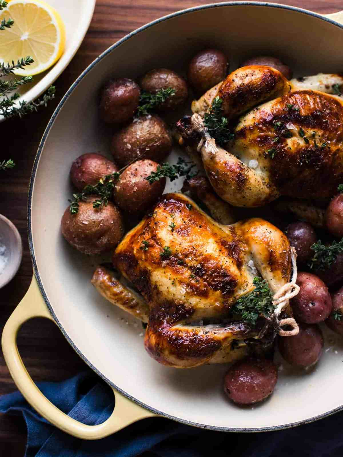 Roasted Buttermilk Brined Cornish Hens and red potatoes in a yellow handled pan.