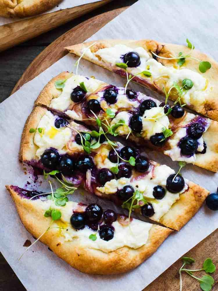 Blueberry, Feta and Honey-Caramelized Onion Naan Pizza on a cutting board.