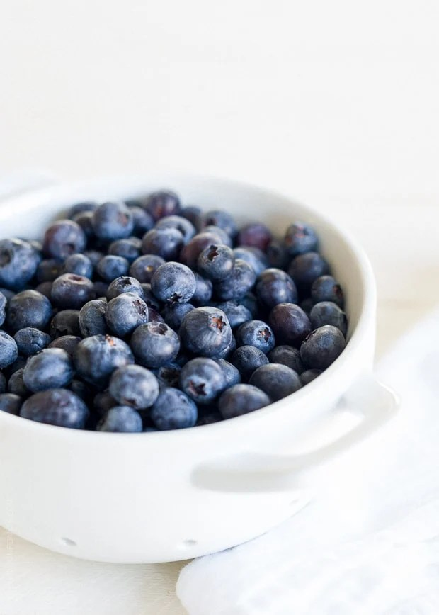 Fresh blueberries in a white colander for Blueberry, Feta and Honey-Caramelized Onion Naan Pizza.