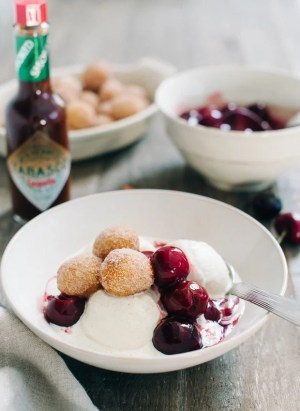 Churro Doughnut Holes with Ice Cream and Cherry Chipotle Sauce | www.kitchenconfidante.com | I think you need a big bowl of ice cream with warm, sugary churro doughnut holes, all drizzled with a sweet and spicy cherry chipotle sauce.