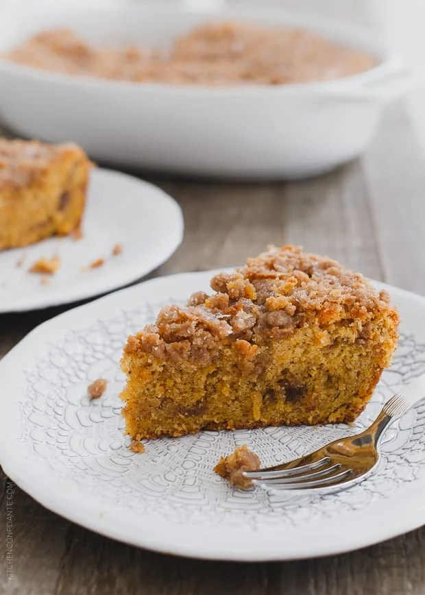 Slice of Buttered Rum and Candied Sweet Potato Crumb Cake on a white plate.