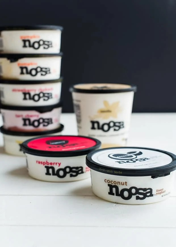 containers of noosa yogurt against a black background